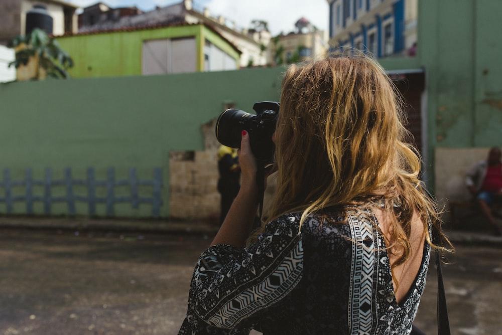woman holding black DSLR camera during daytime