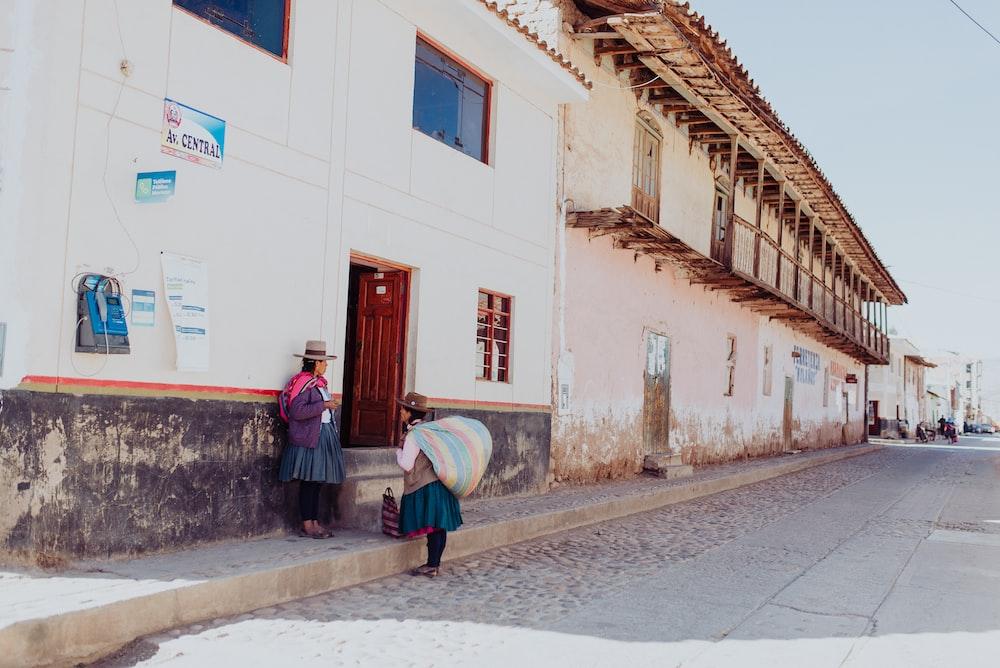 two women talking while standing near building duting daytime