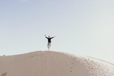 man jumping on brown sand during daytime