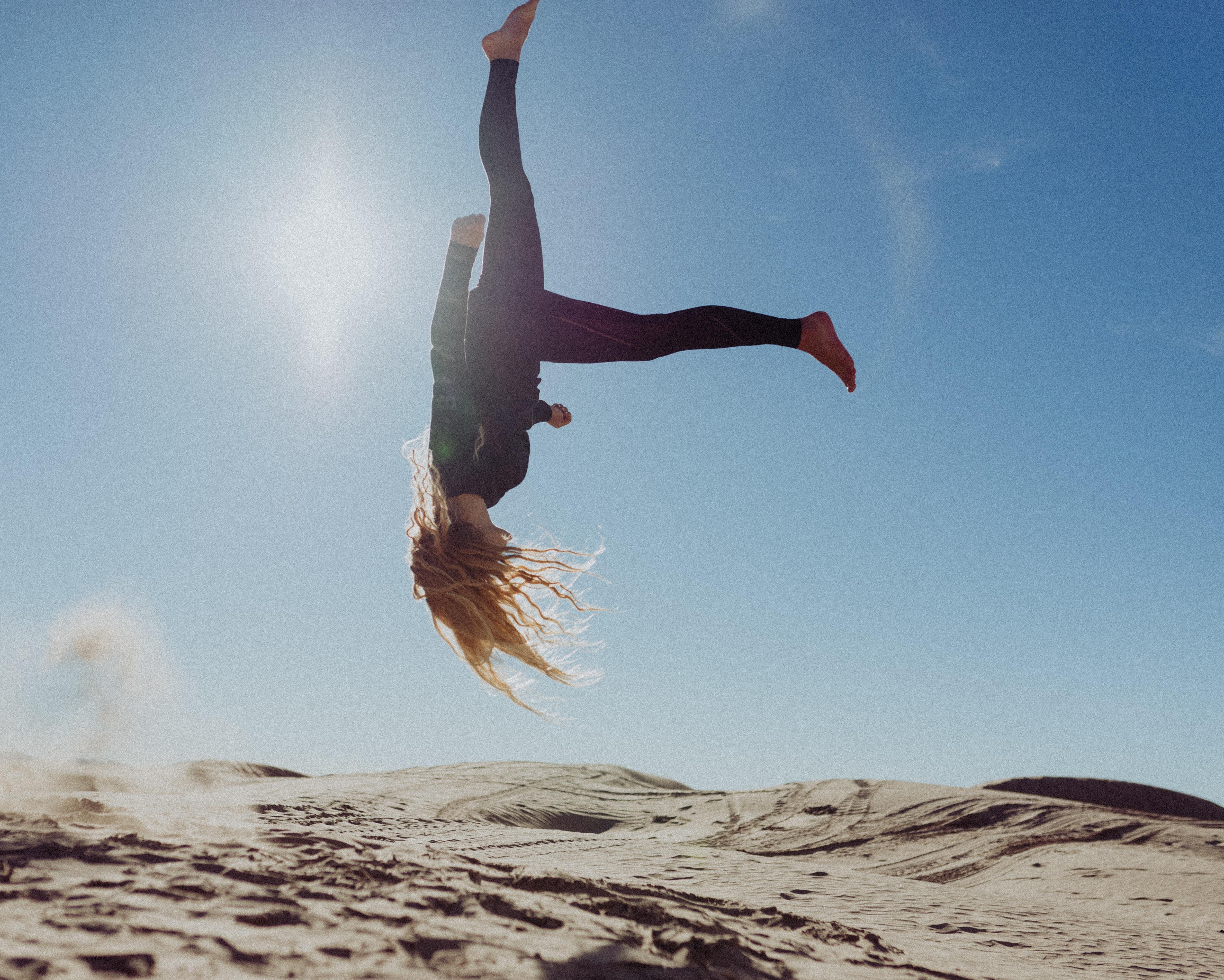 woman back flip under blue sky