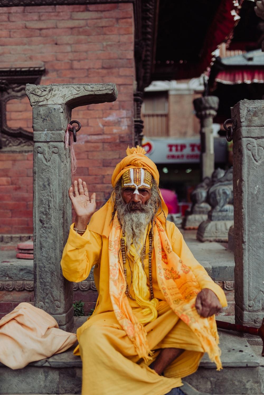 man wearing yellow long-sleeved coat sitting near pillar