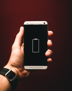 person holding low battery smartphone