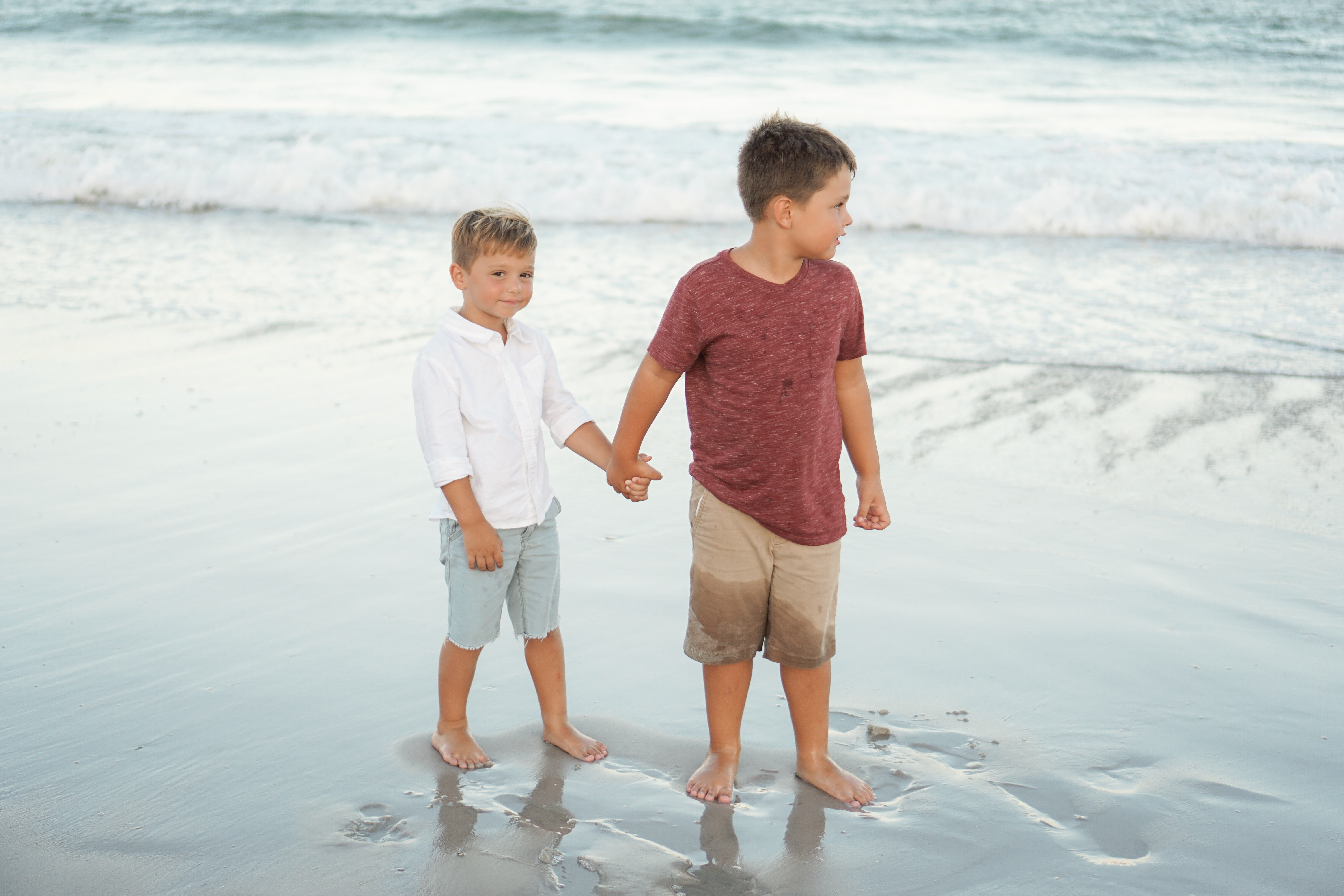 two boy's standing on beach sand
