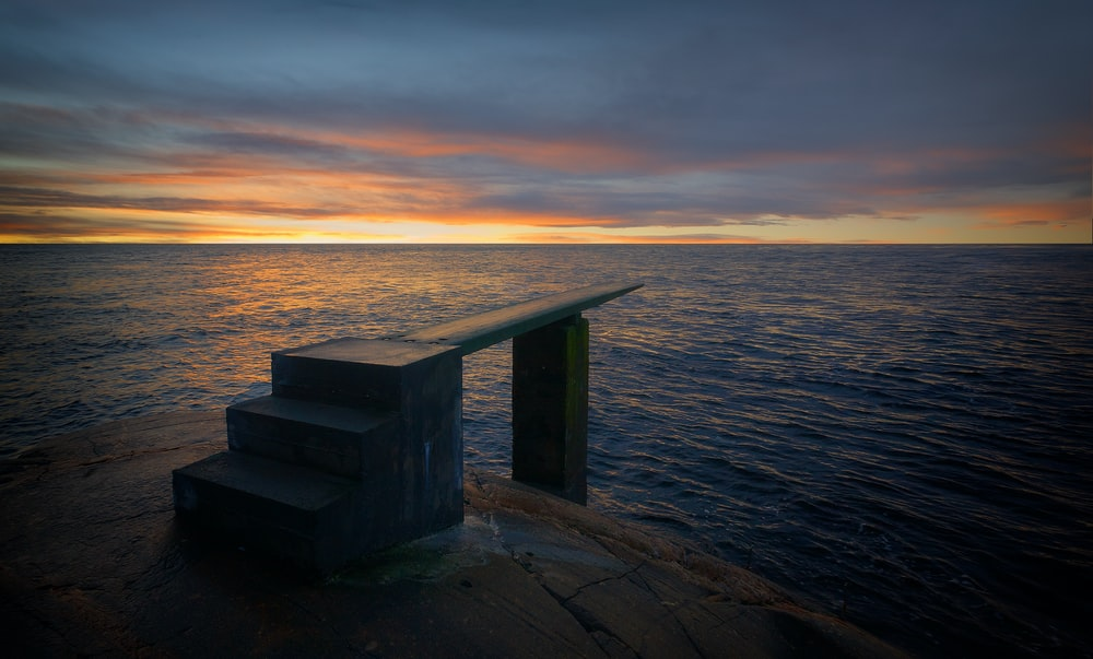 grey stairs on body of water during golden hour