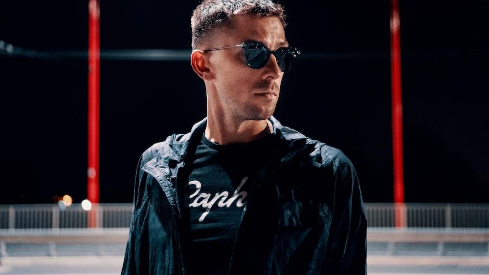man wearing black jacket and sunglasses close-up photo