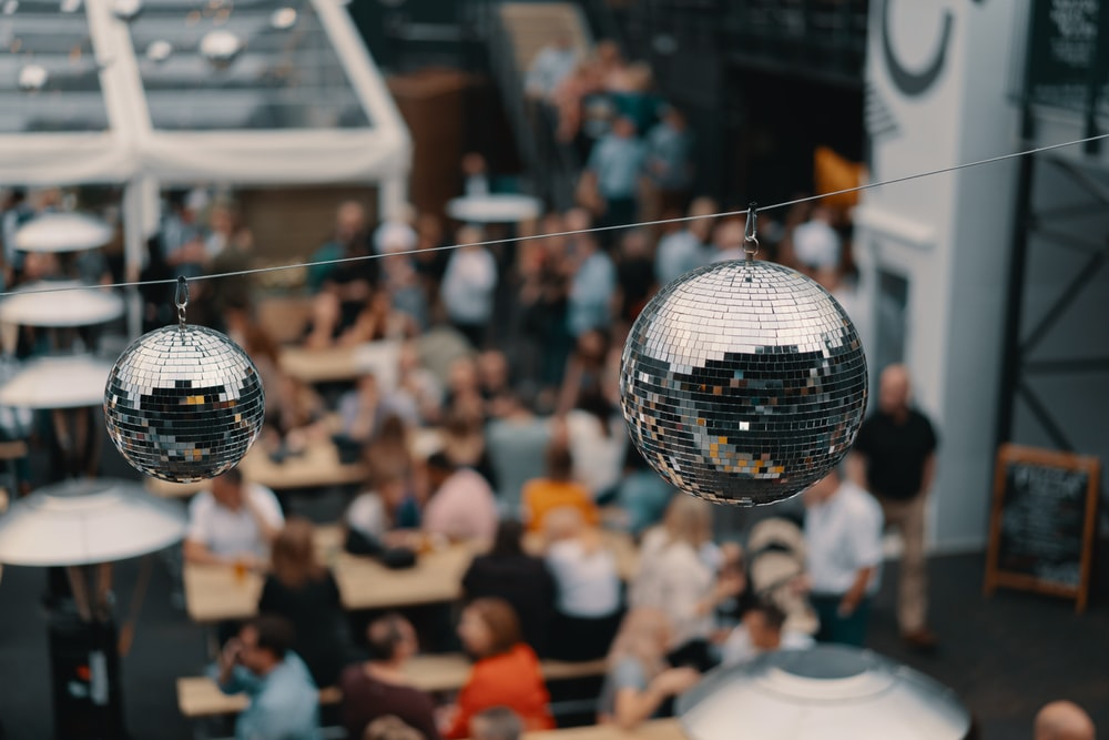 two hanging silver disco balls in shallow focus photography