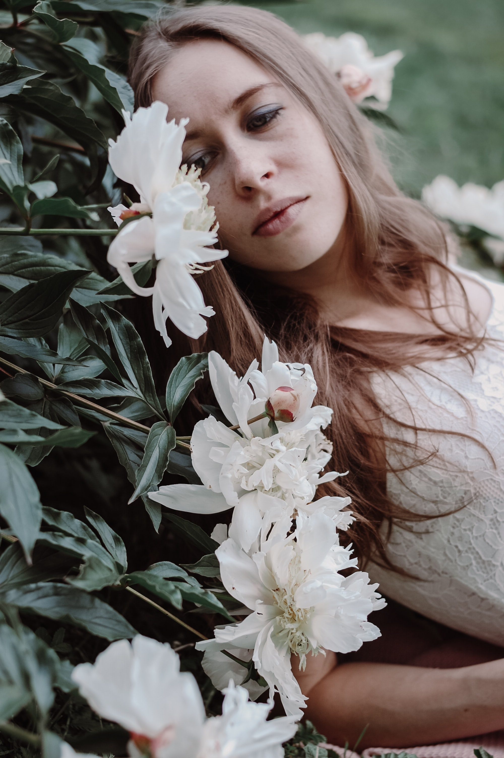 woman lying on white flowers