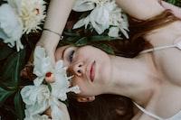 woman lying near white petaled flower