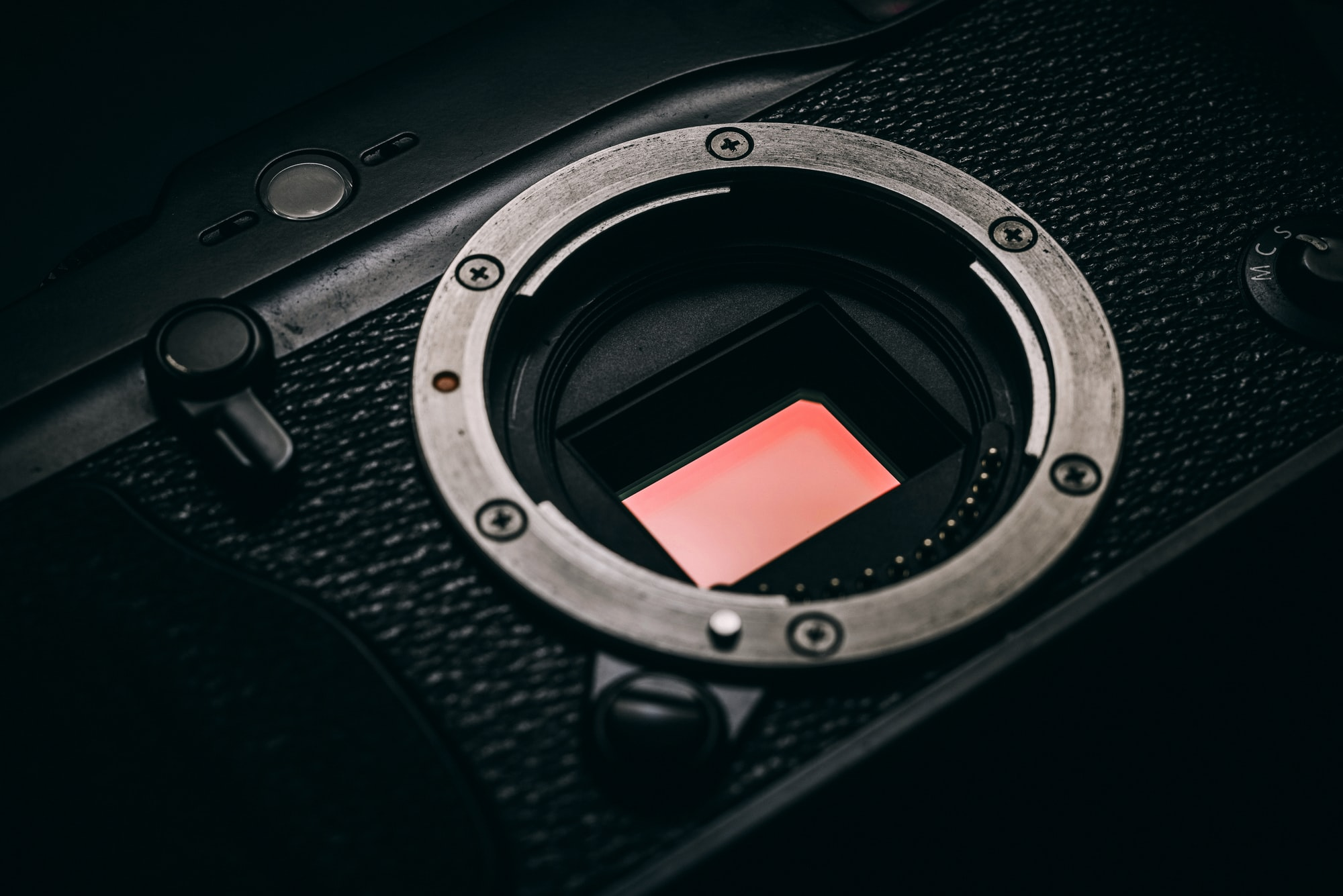 A close-up image of a digital camera with no lens and shutter raised so that the sensor is visible.