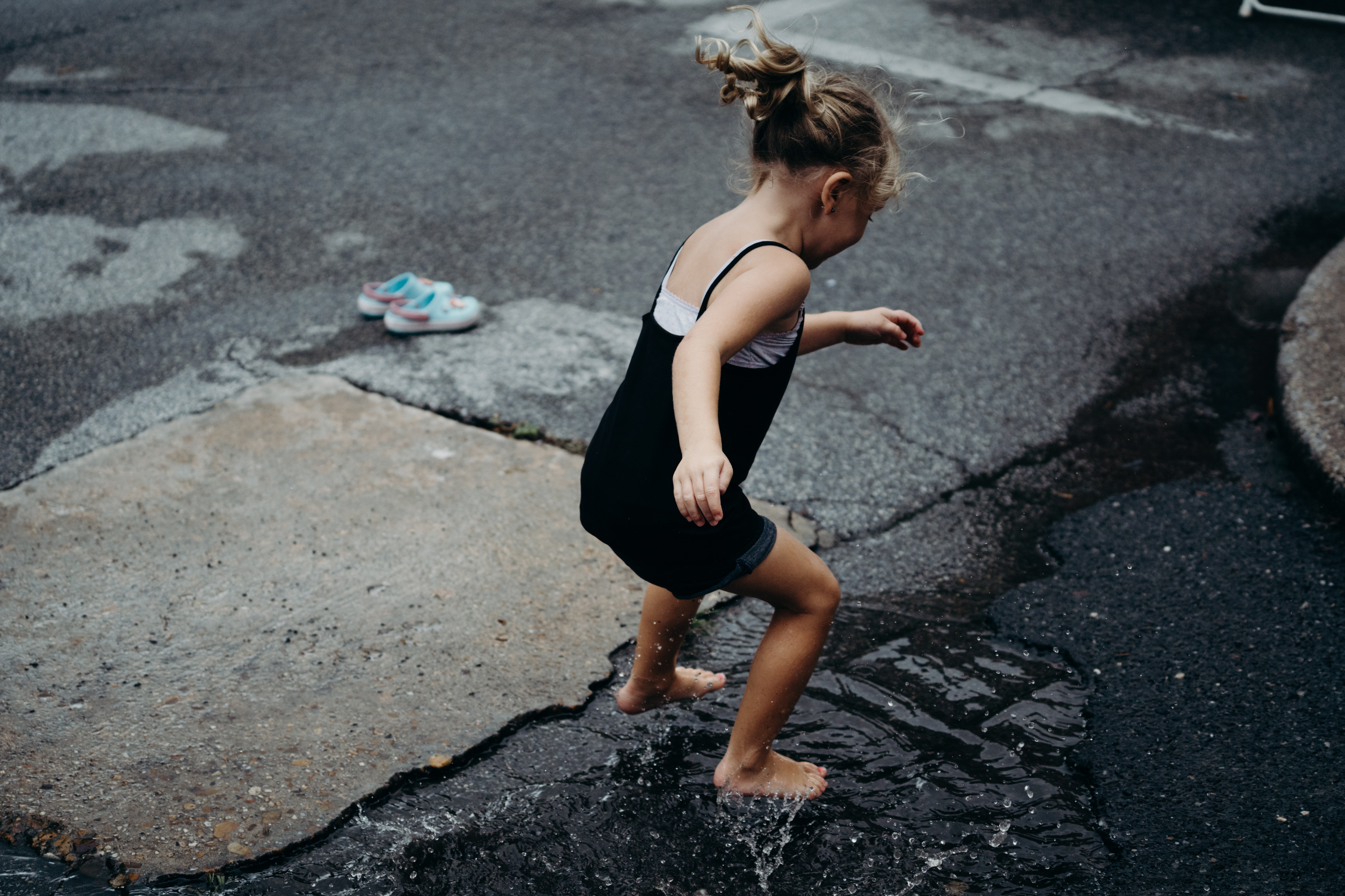 girl jumps in the water surface on asphalt road during daytime