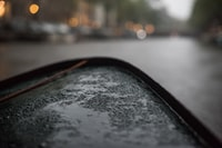 selective focus photography of black surface with water dew