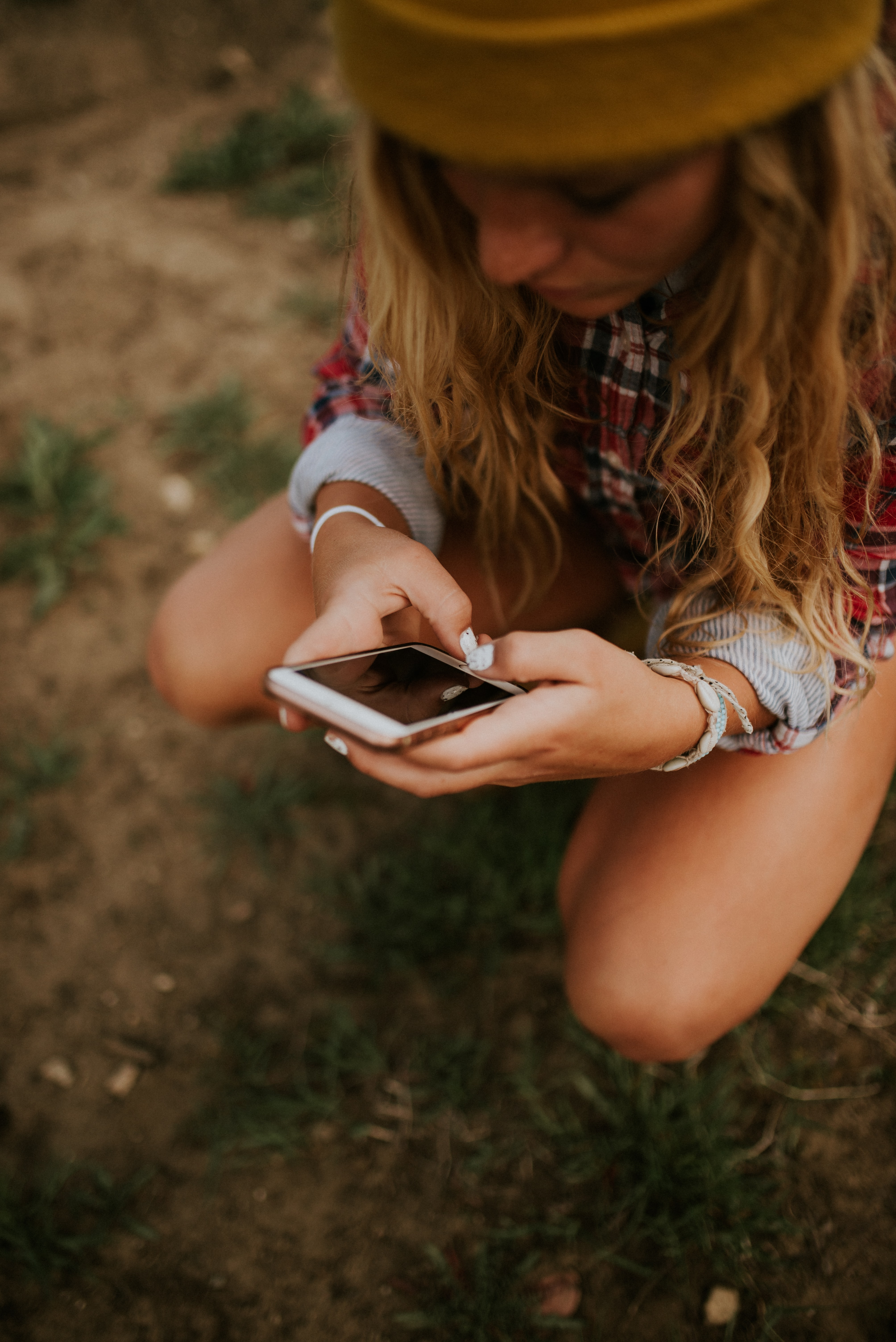 woman squatting on grass field while using white smartphone