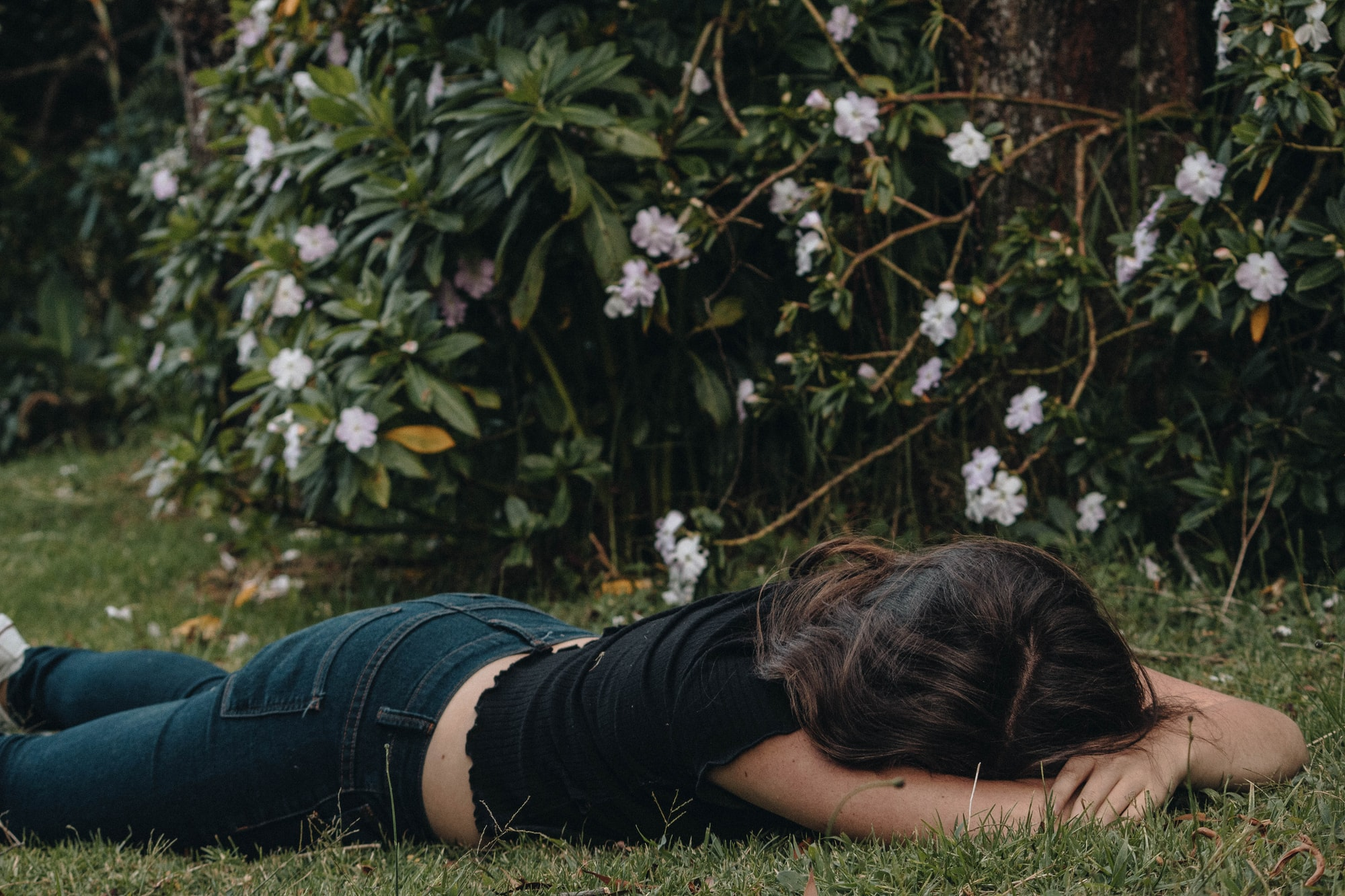 A woman is lying down on a park face down with her head on her elbow.