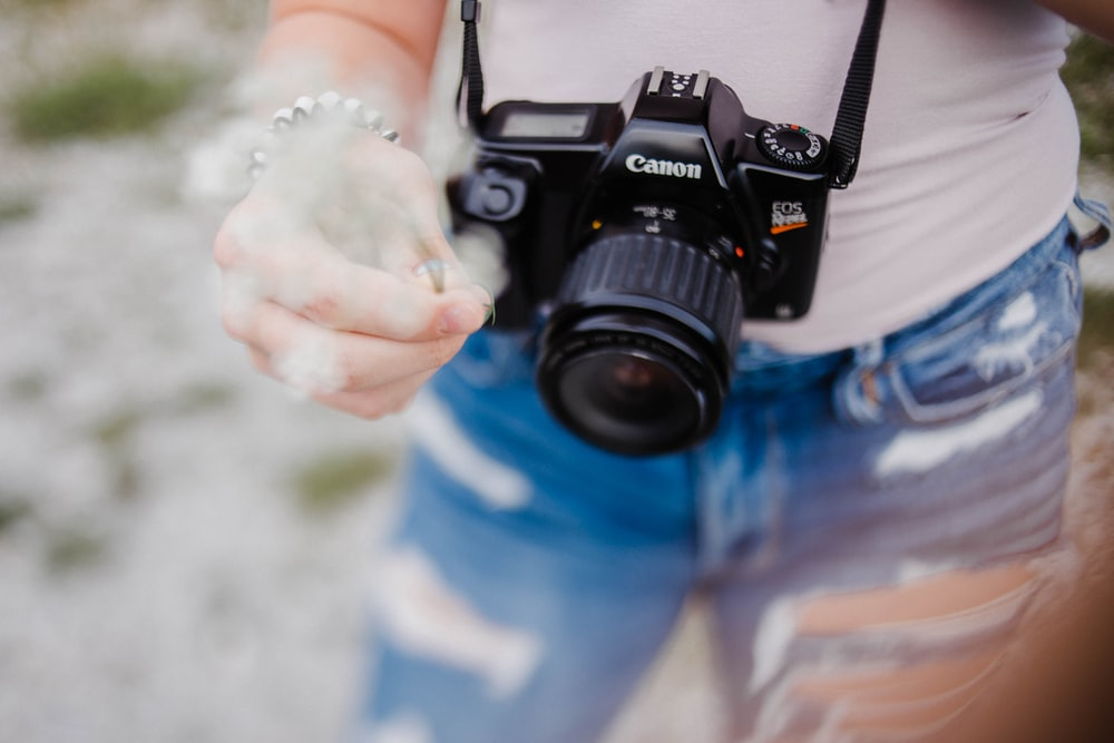 person carrying black Canon DSLR camera