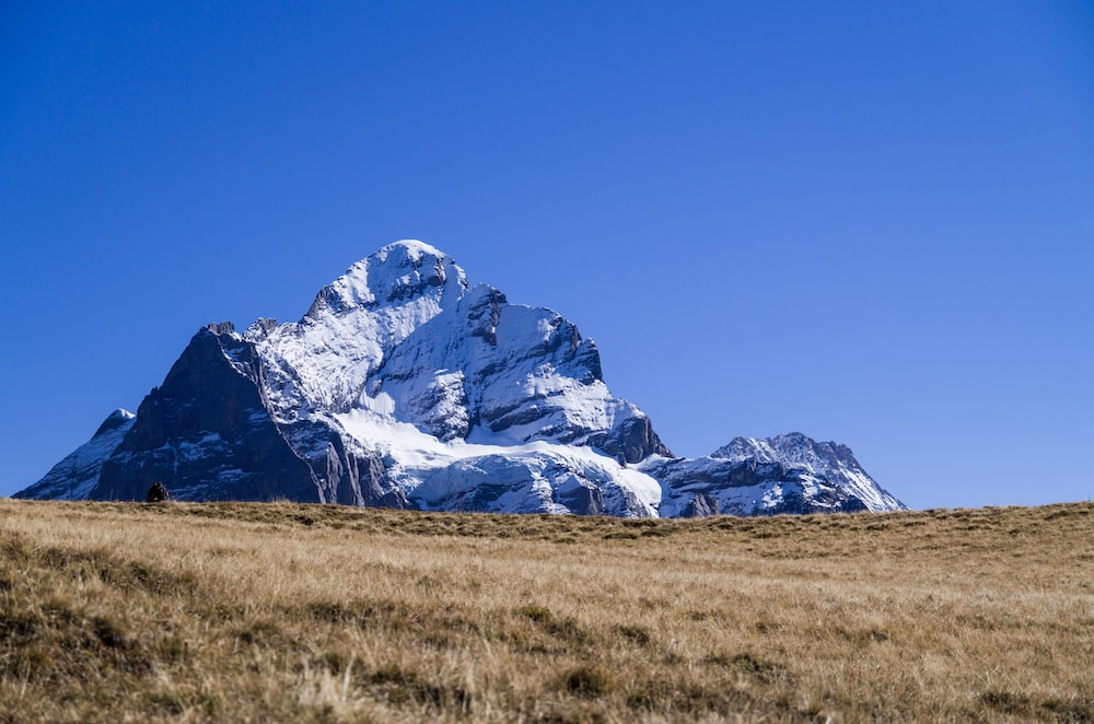 snow-covered mountain under blue and white skies during daytime