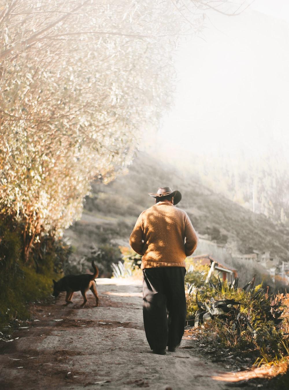 man wearing brown sweater walking on the field near the dog