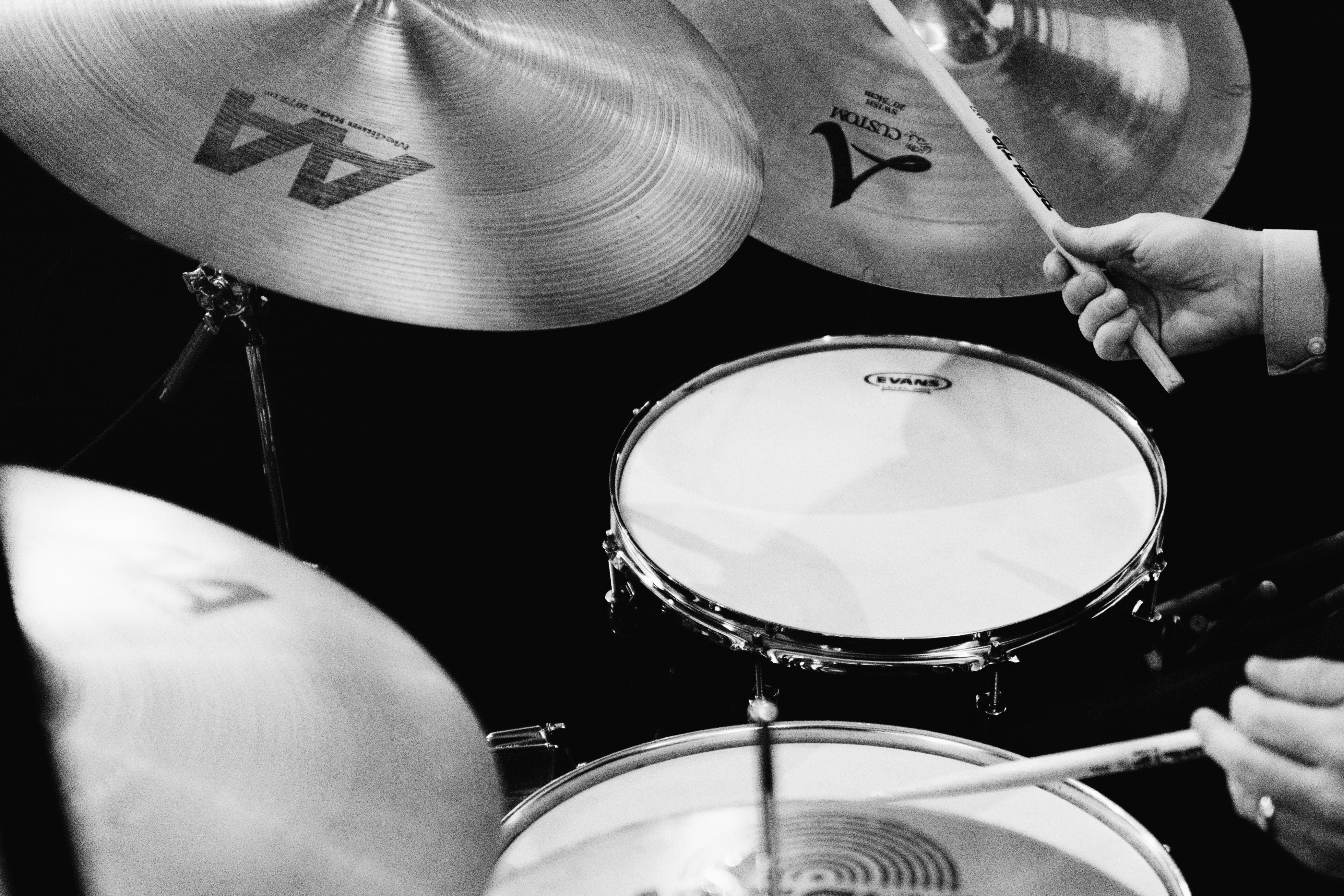 grayscale photography of man playing drums
