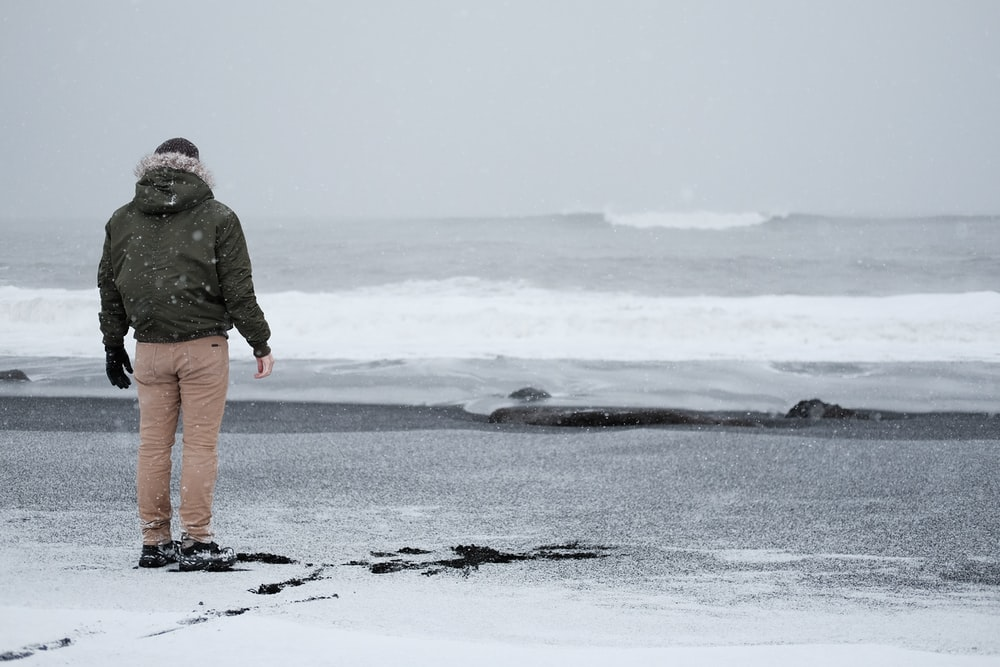 person in grey jacket and brown standing standing at the shore