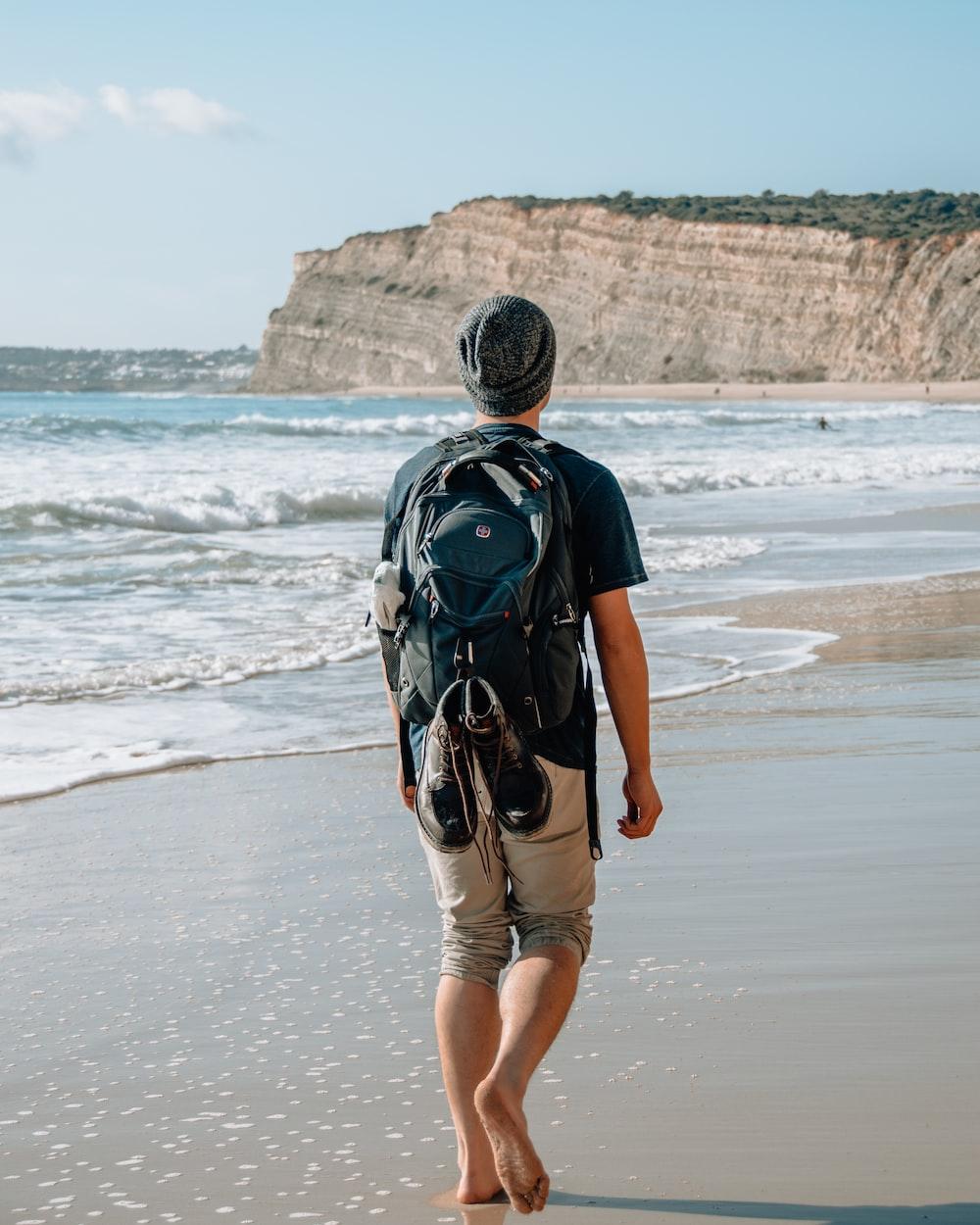 man walking on seashore near cliff
