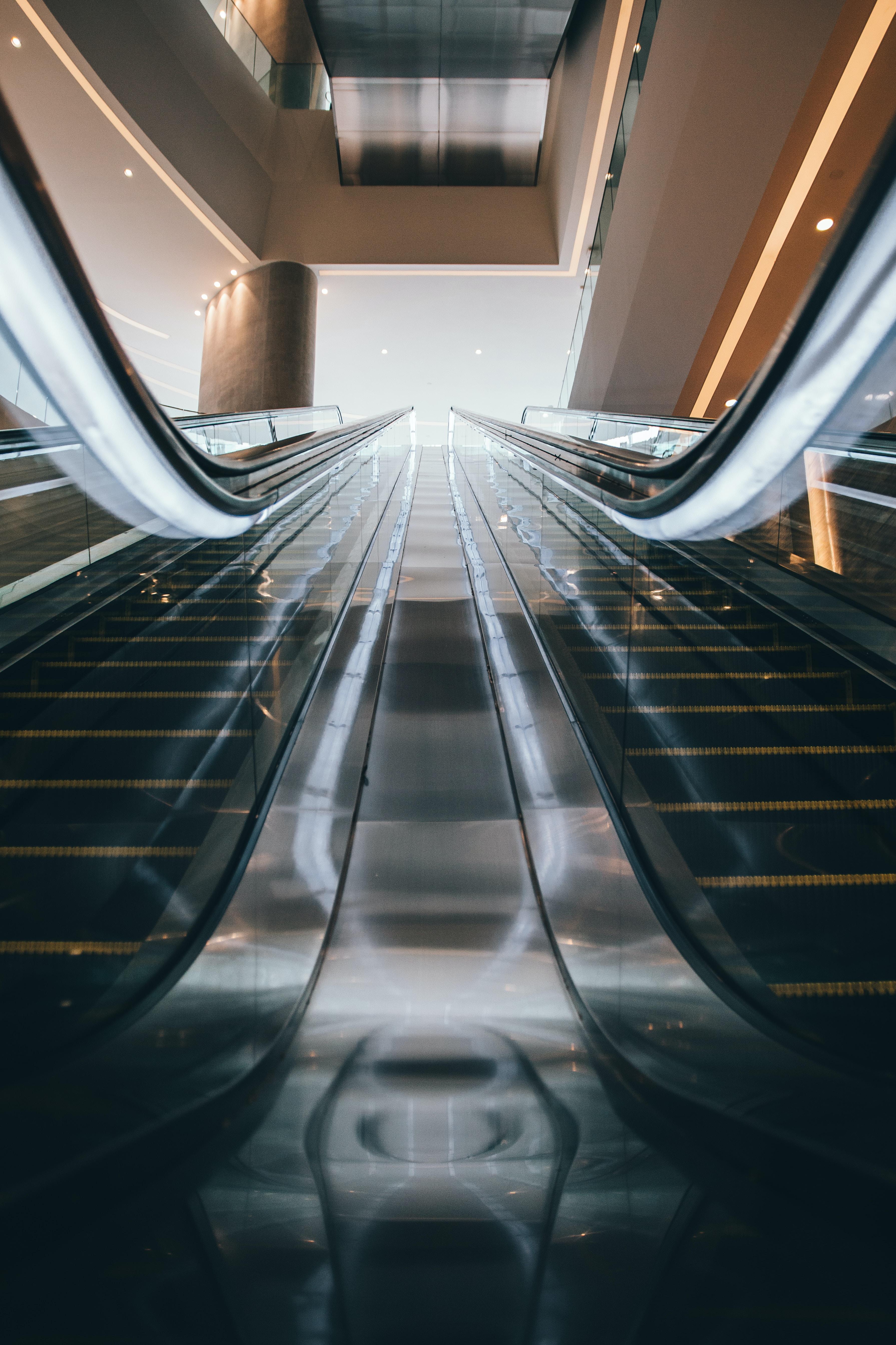 two black escalators inside white building