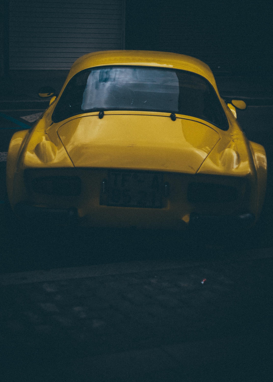 yellow car parked at sidewalk
