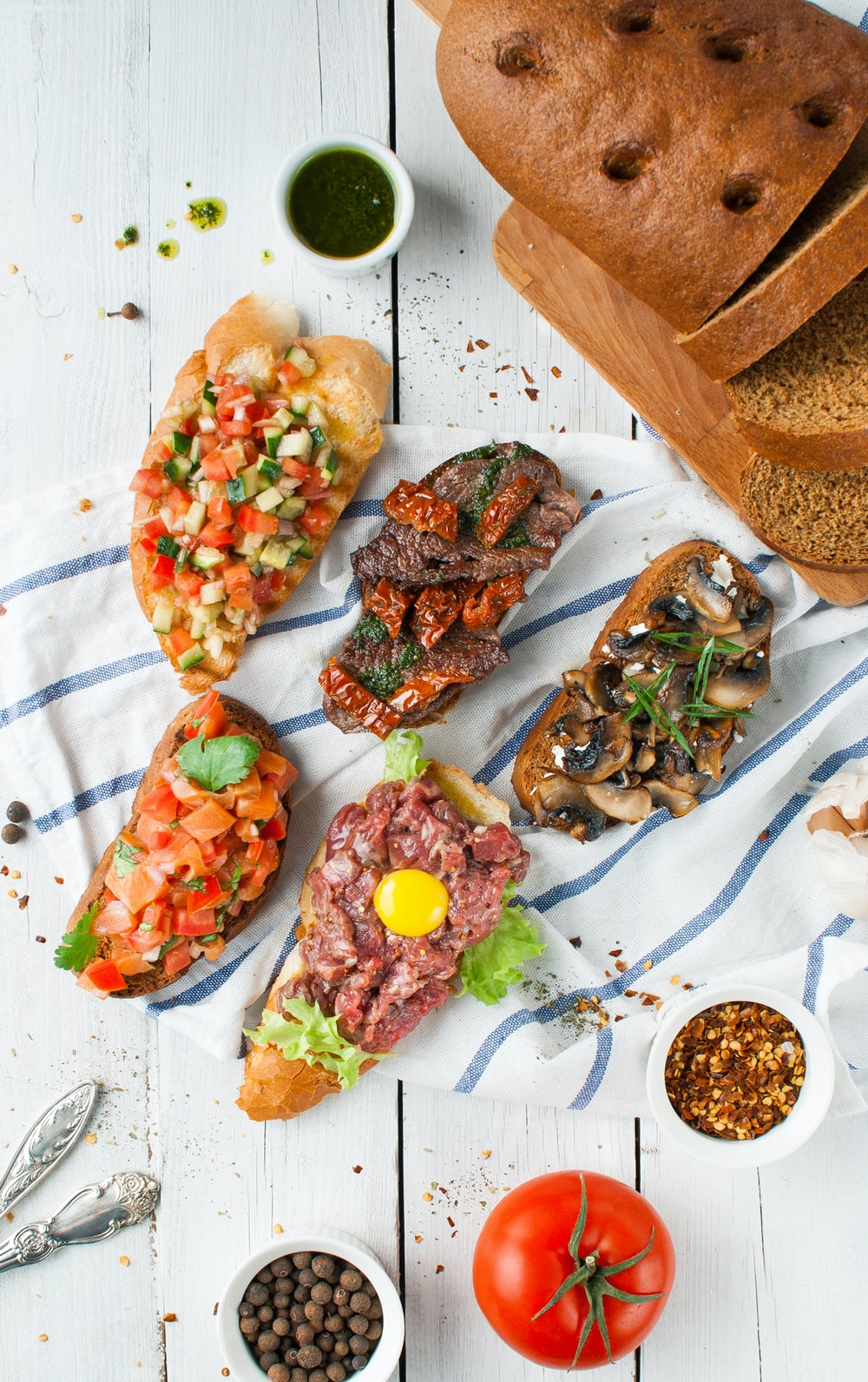 flay lay photography of sliced breads with beef and vegetables on top and dips
