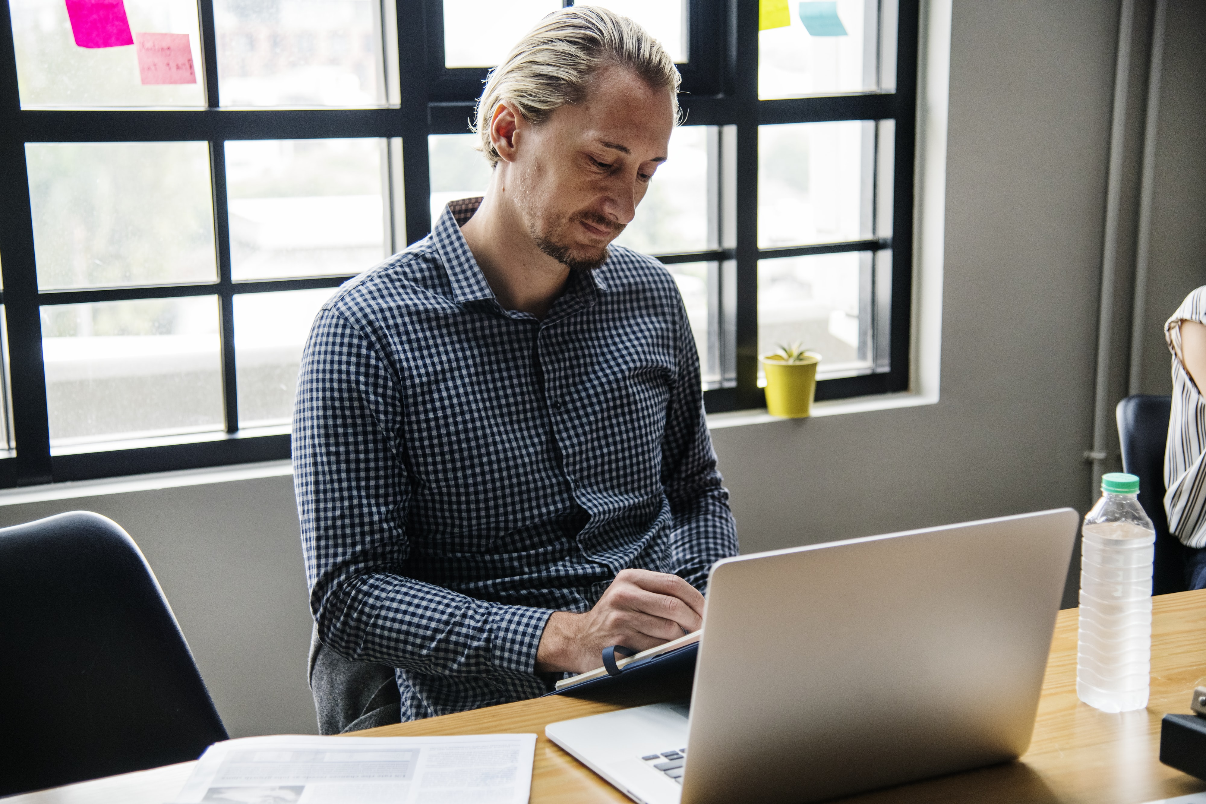 man in blue dress shirt using MacBook Pro on table