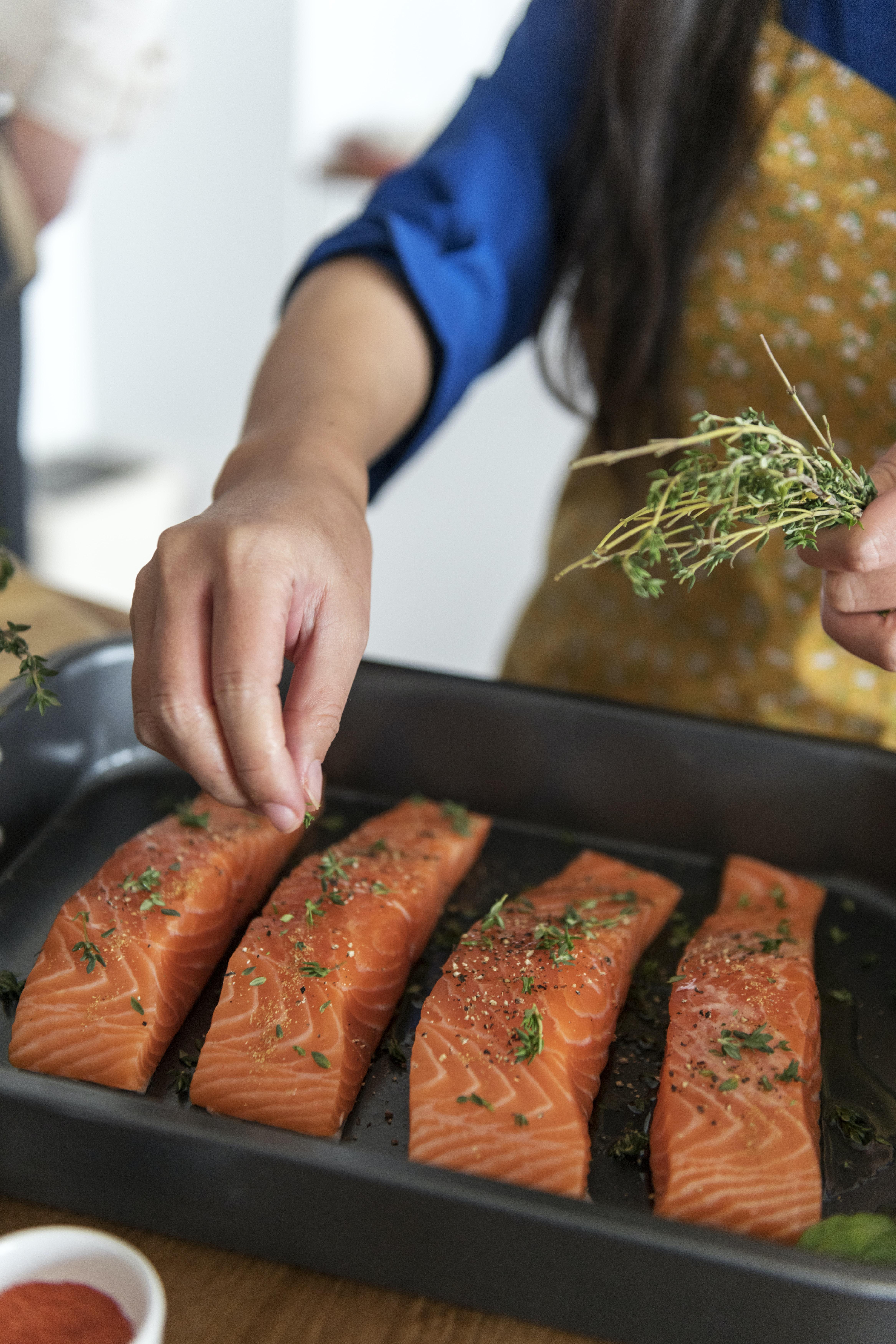 woman putting seasonings on salmon