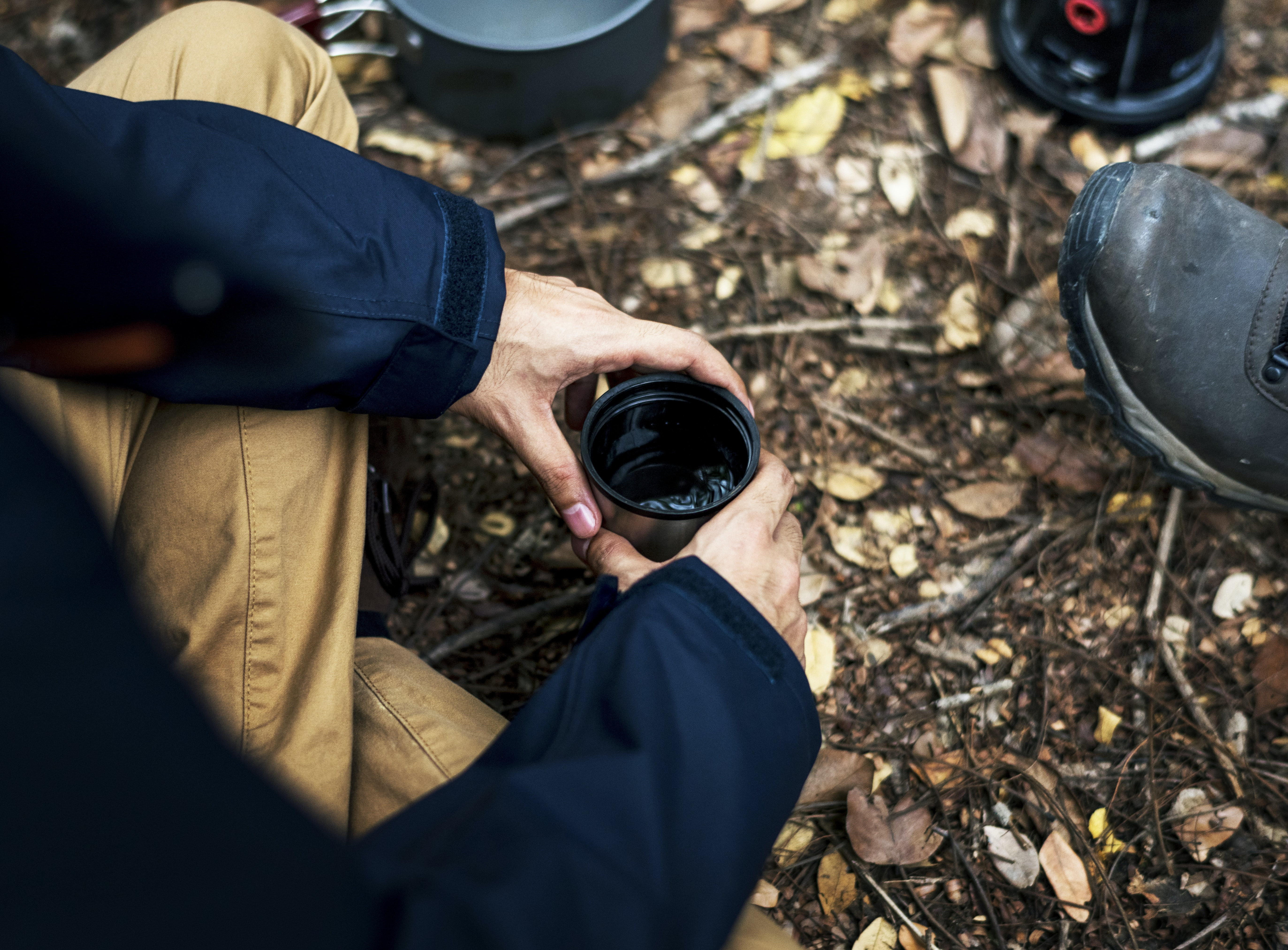 person holding black cup while sitting on ground