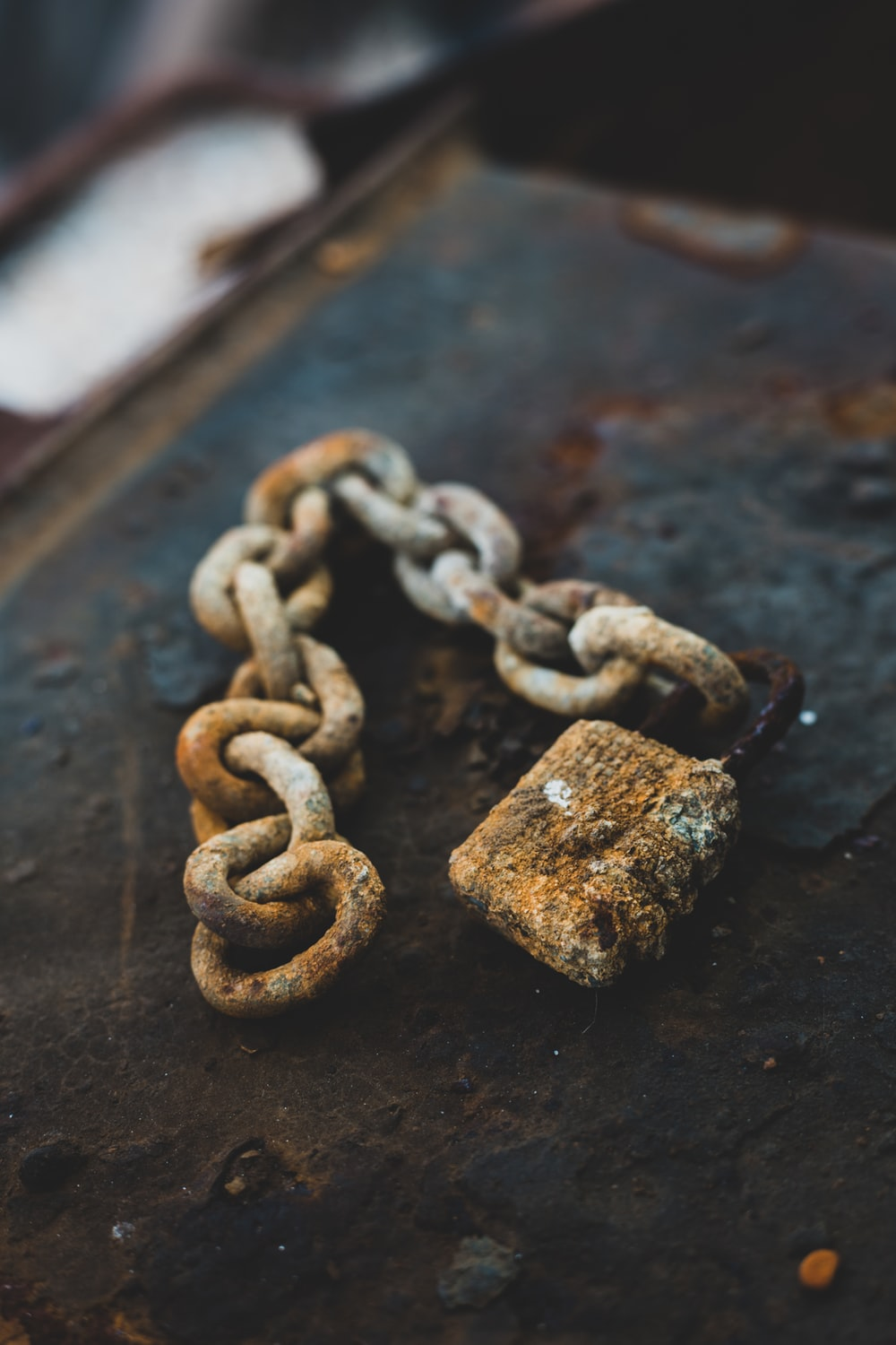 selective focus photography of gray rust-covered chain and padlock