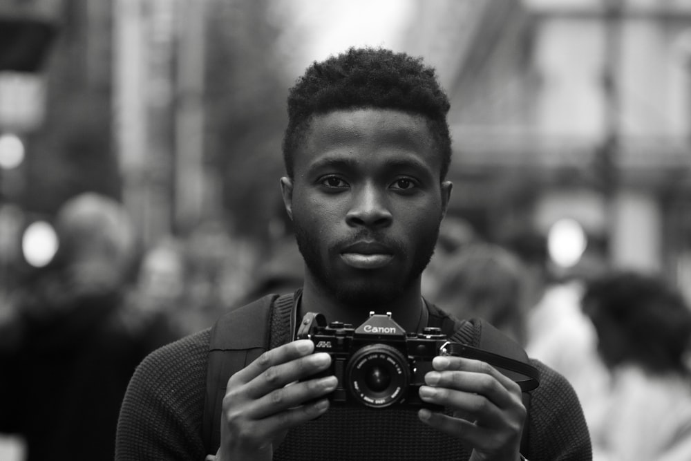 grayscale photo of man holding Canon camera