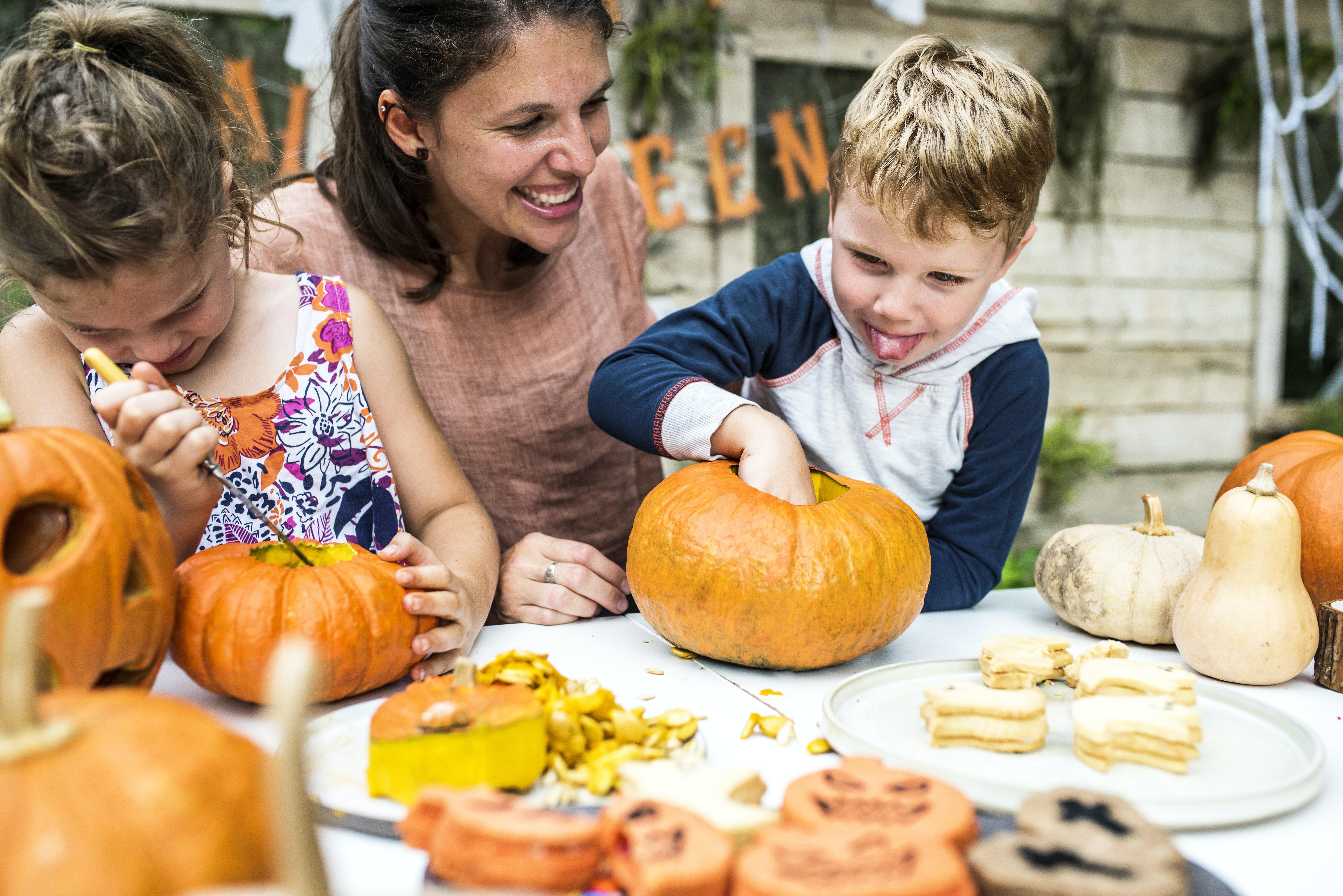 boy holding pumpkin on table top near woman