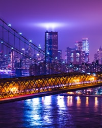 photography of suspension bridge and high-rise building during nighttime