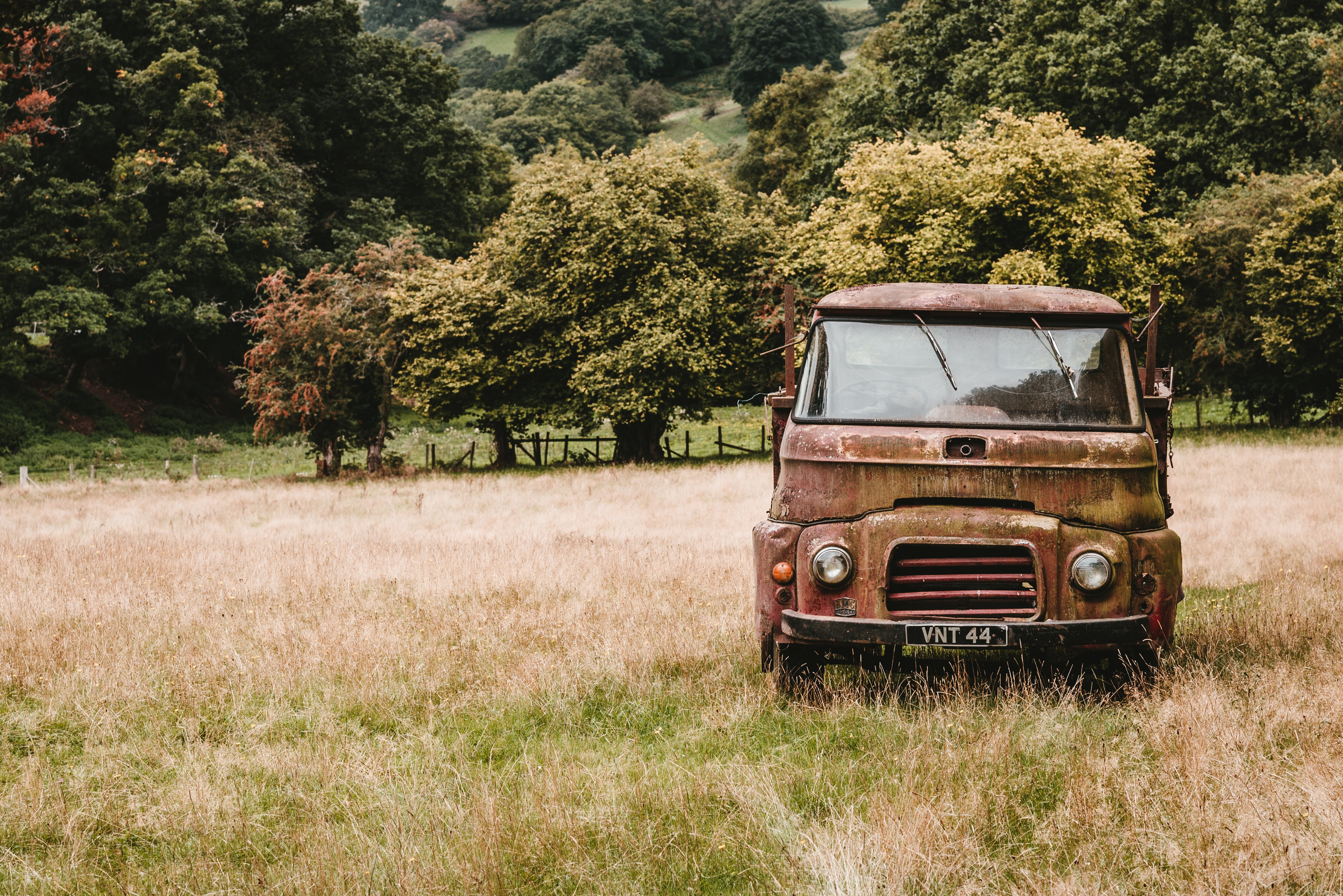 abandoned brown vehicle in the middle of grassland