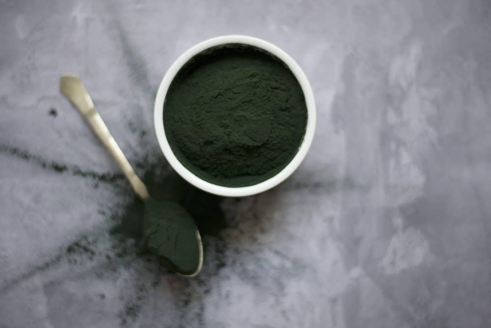 flat lay photography of green powder in pot