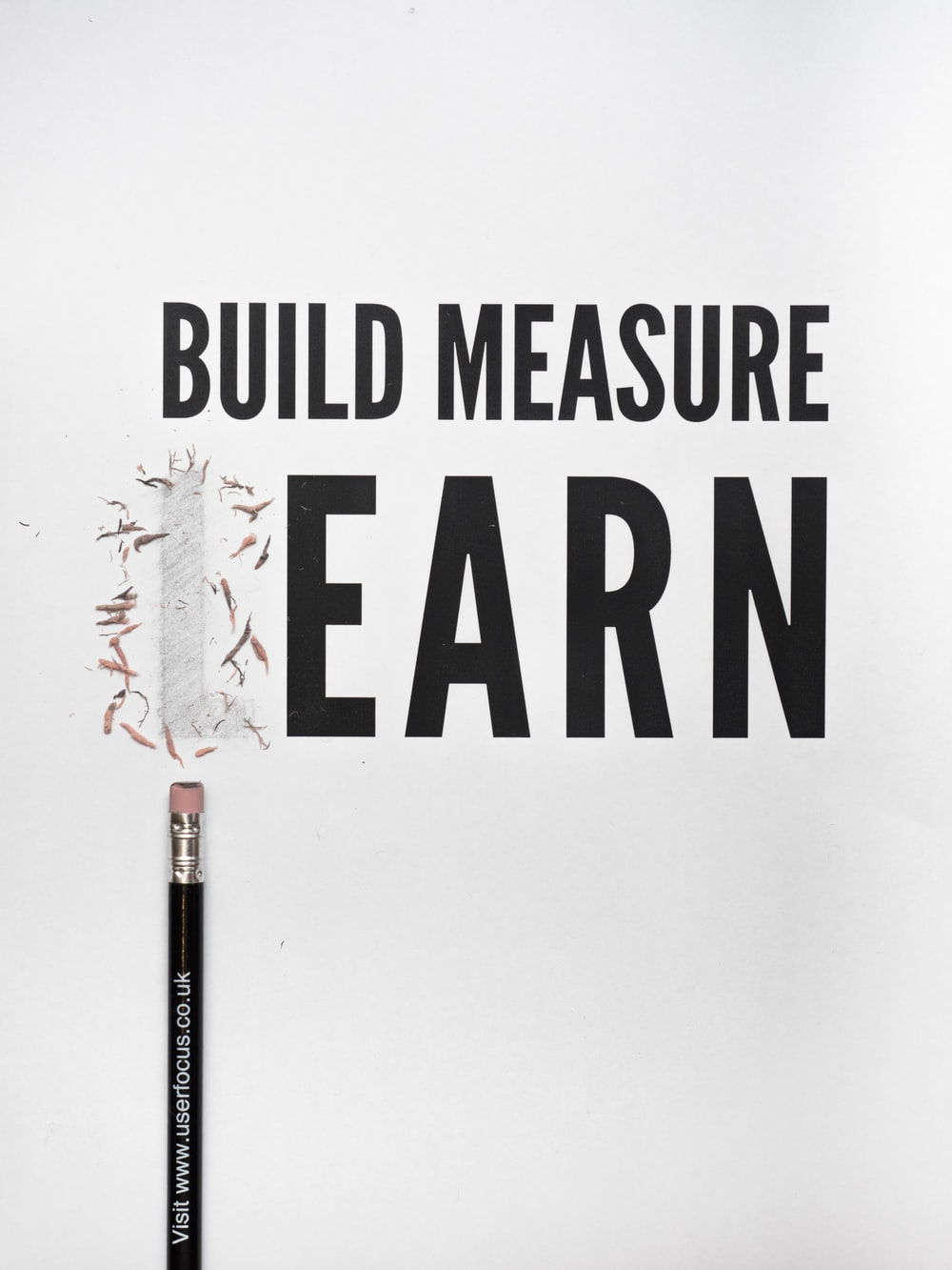 black pencil with build measure earn text overlay