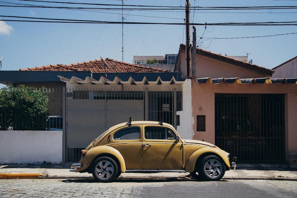 beige Volskwagen Beetle parked outside house