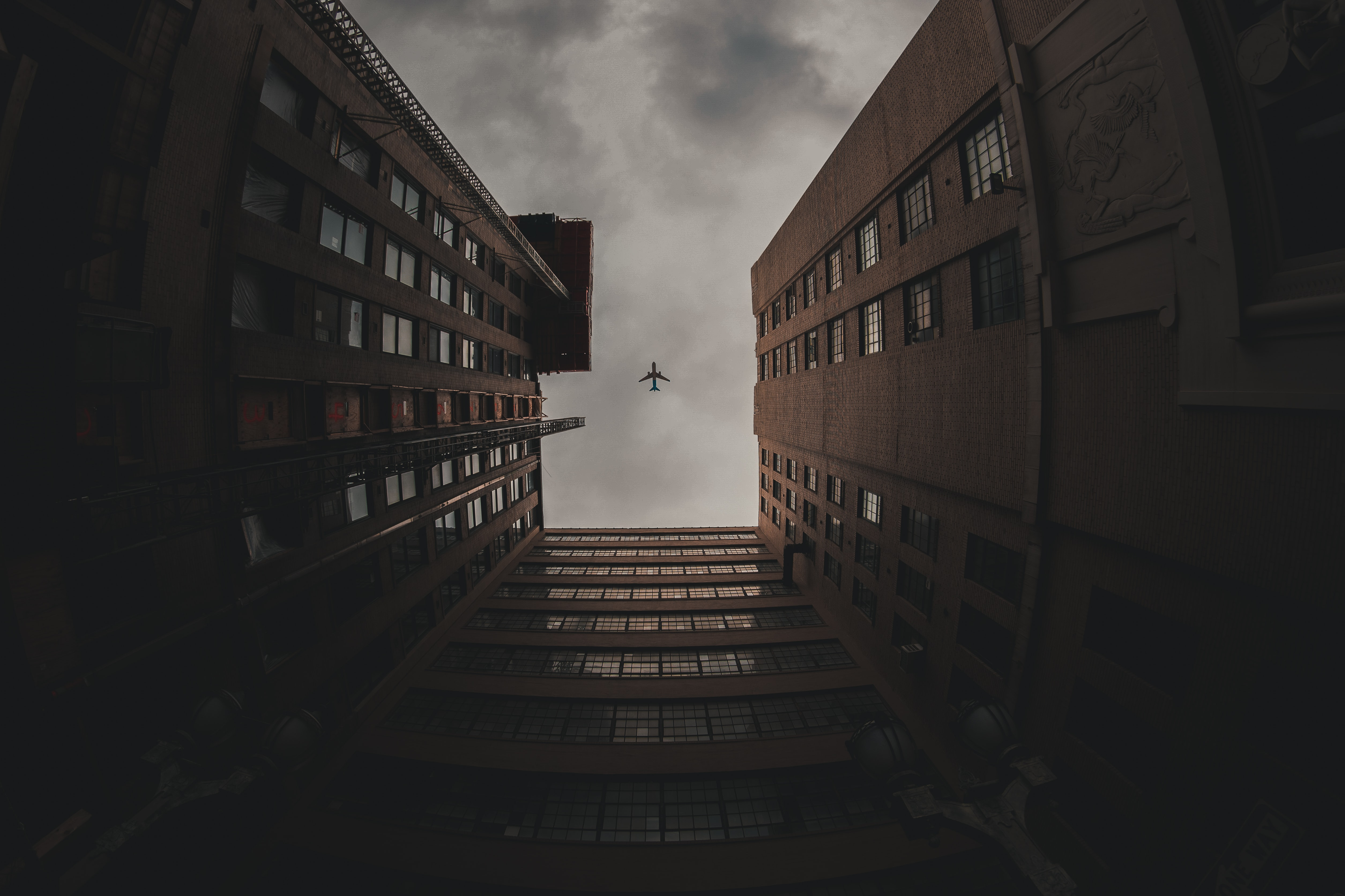 low-angle photo of airliner in flight above high-rise buildings