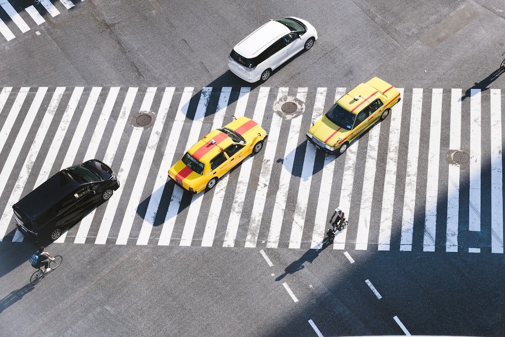aerial photo of four vehicles on road at daytime
