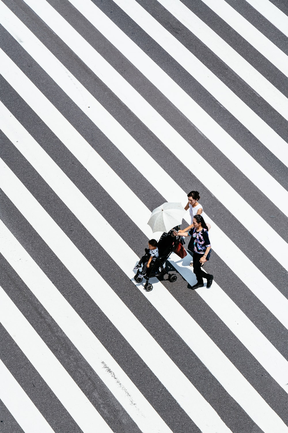 two women and baby crossing striped floor