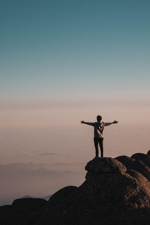 man standing beside cliff