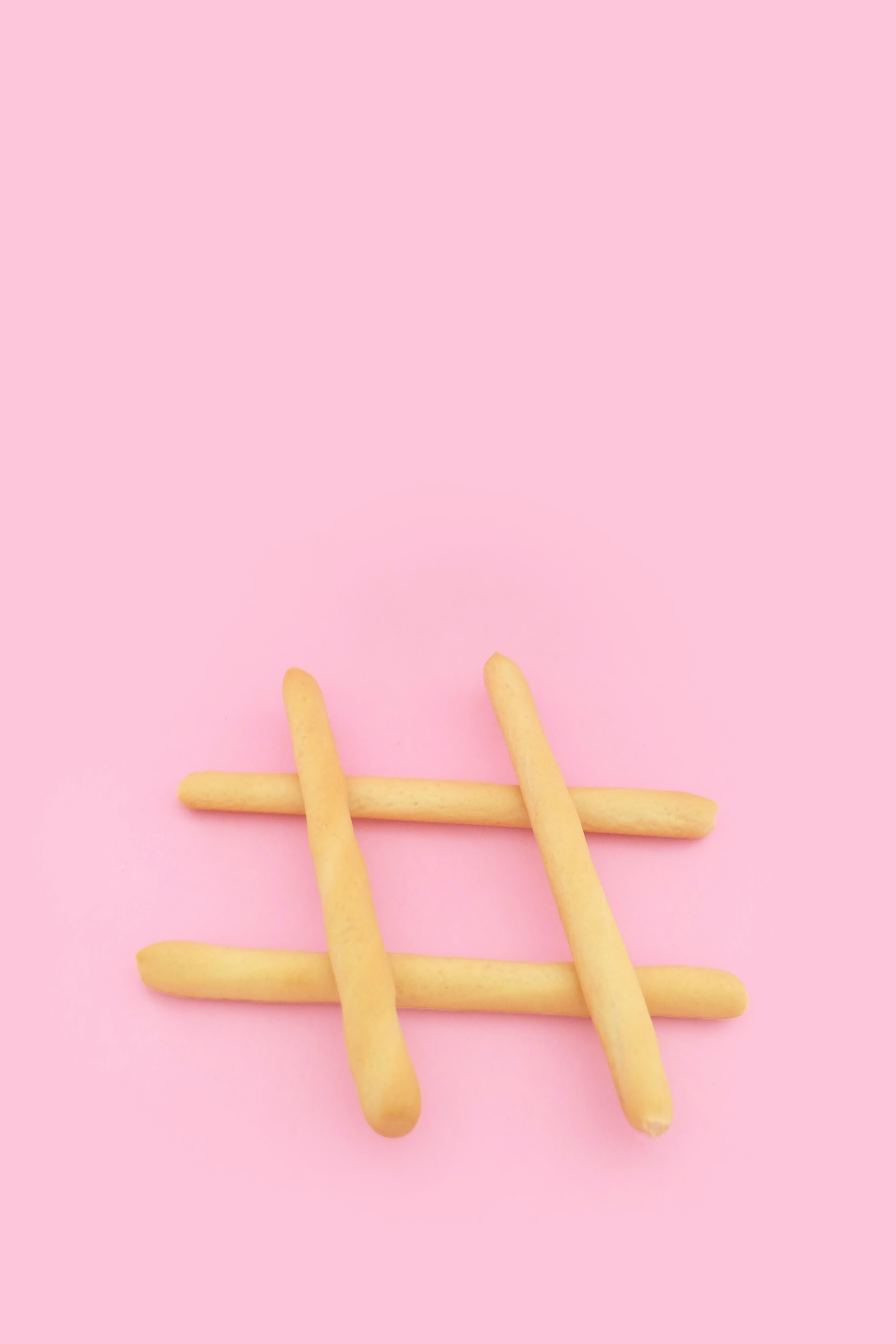 four brown wooden sticks on pink surface