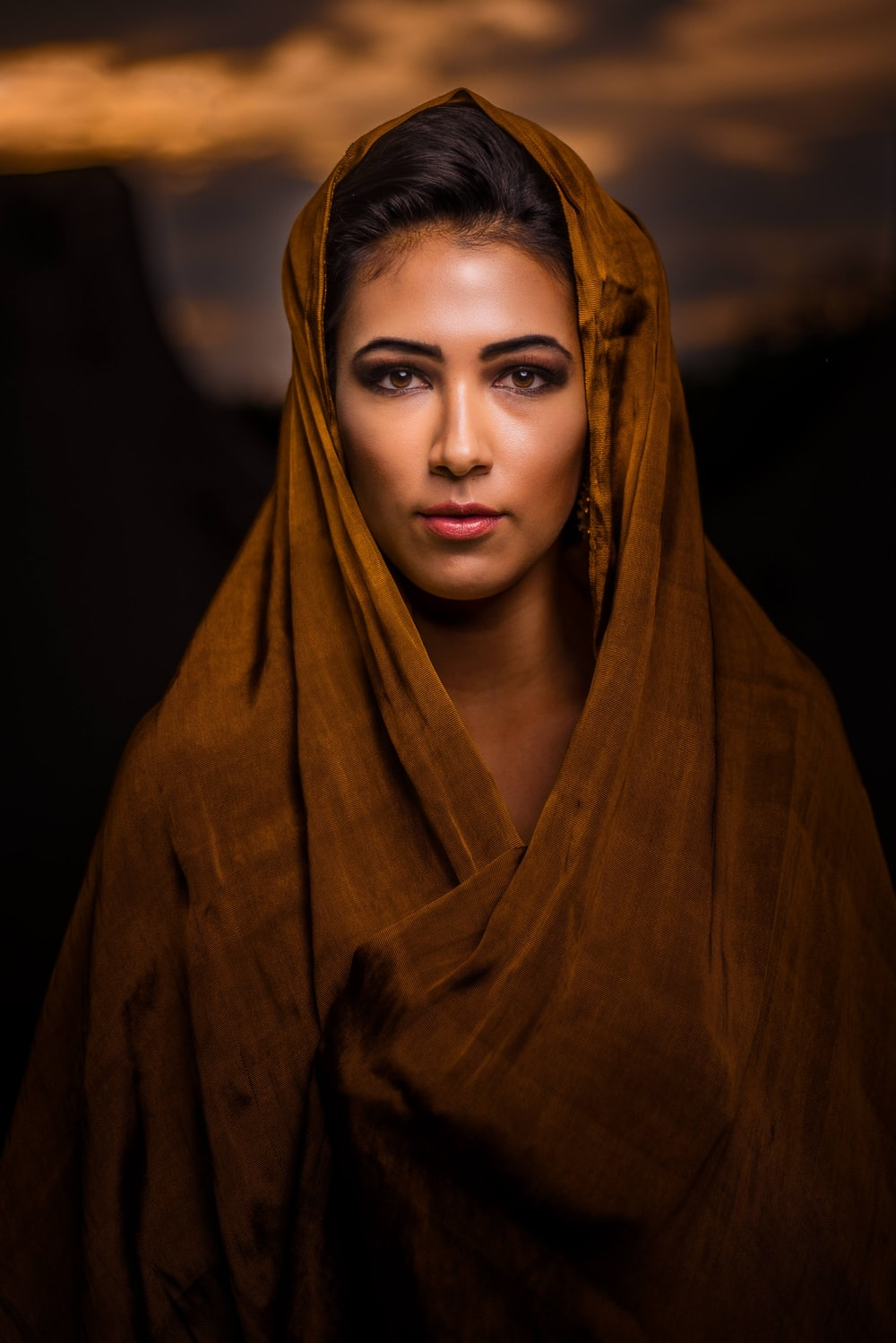 portrait photography of woman wearing brown headscarf
