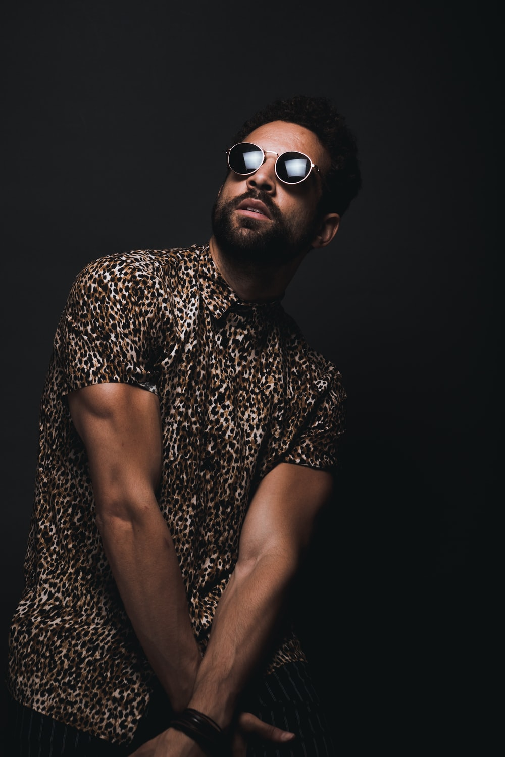 man wearing brown and black leopard print button-up T-shirt and black sunglasses crossing hands down while looking up