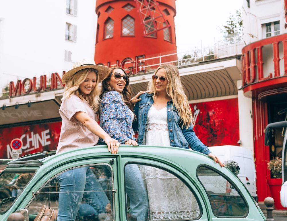 three women standing on car roof near Mochine store
