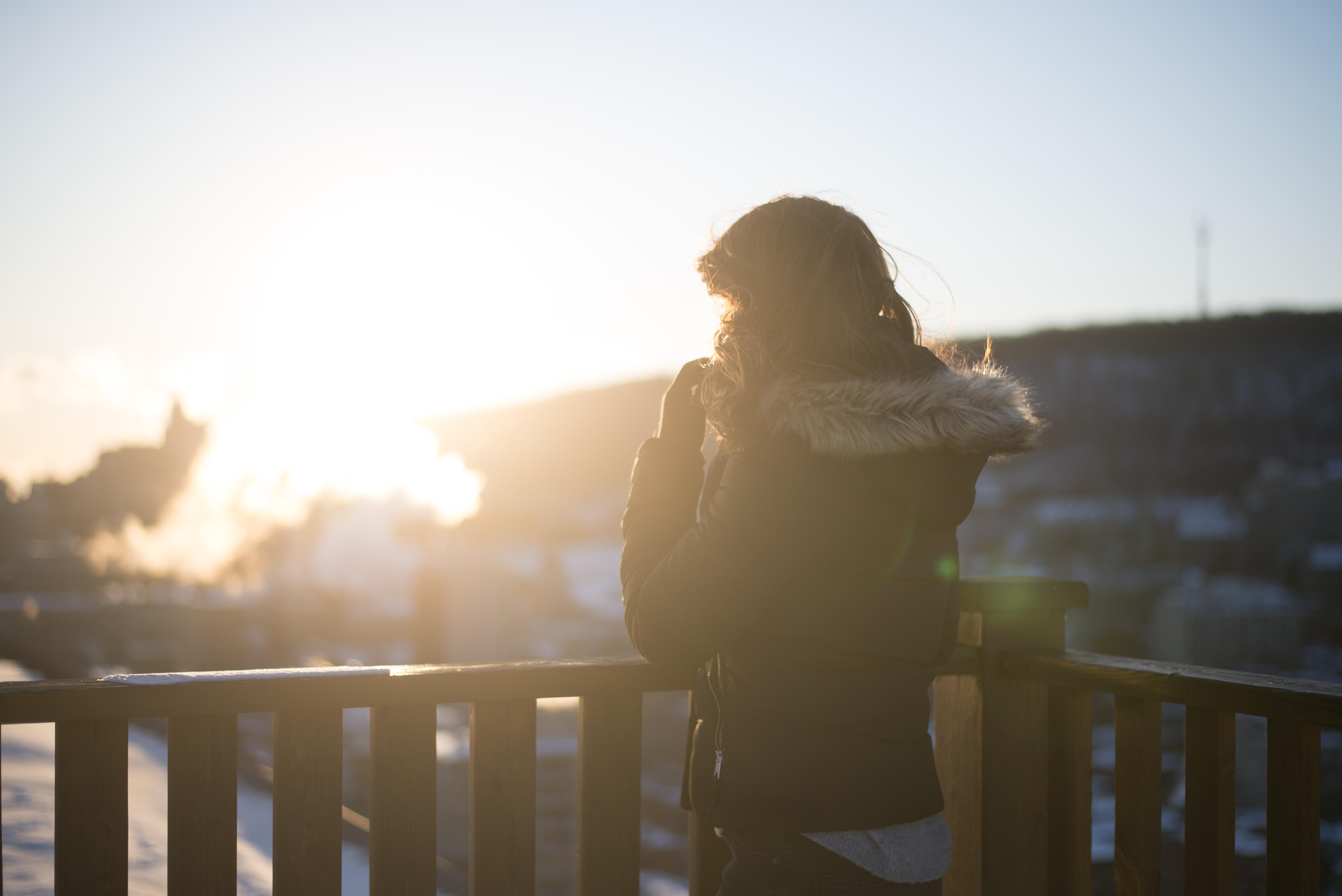 person wearing hoodie standing near brown wooden balustre