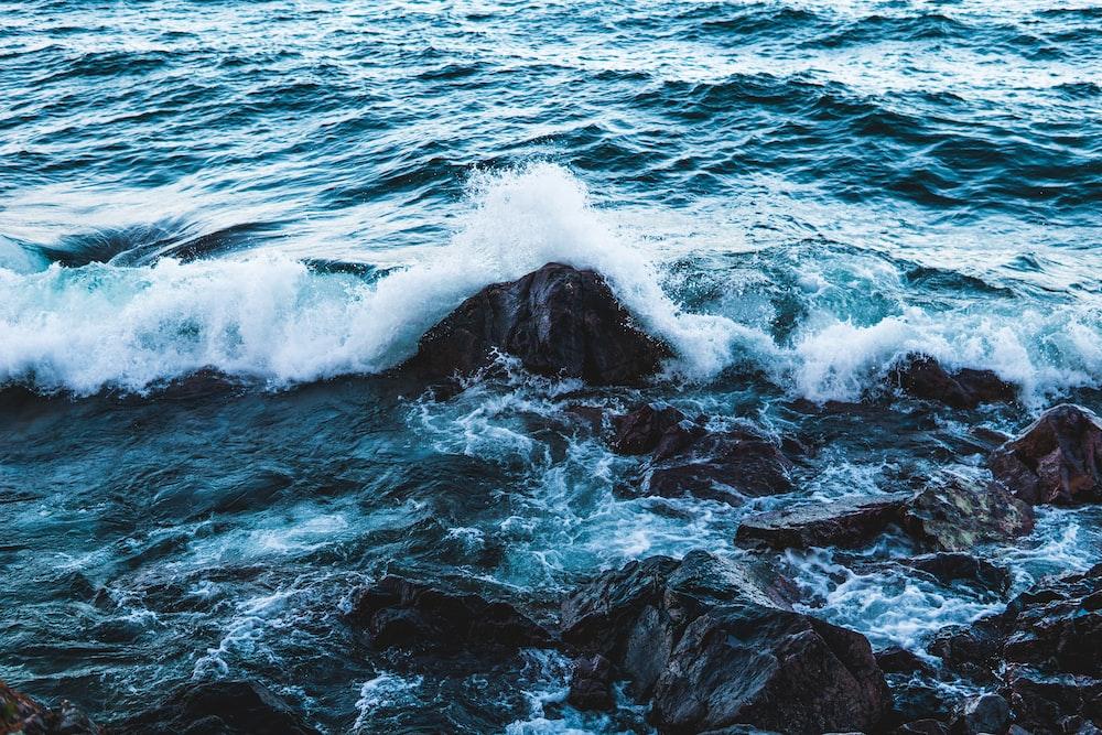 blue ocean water on brown concrete rocks