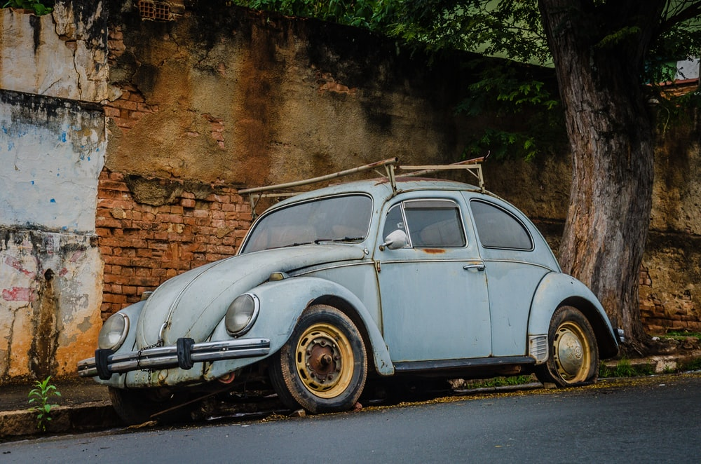blue Volkswagen Beetle coupe on road