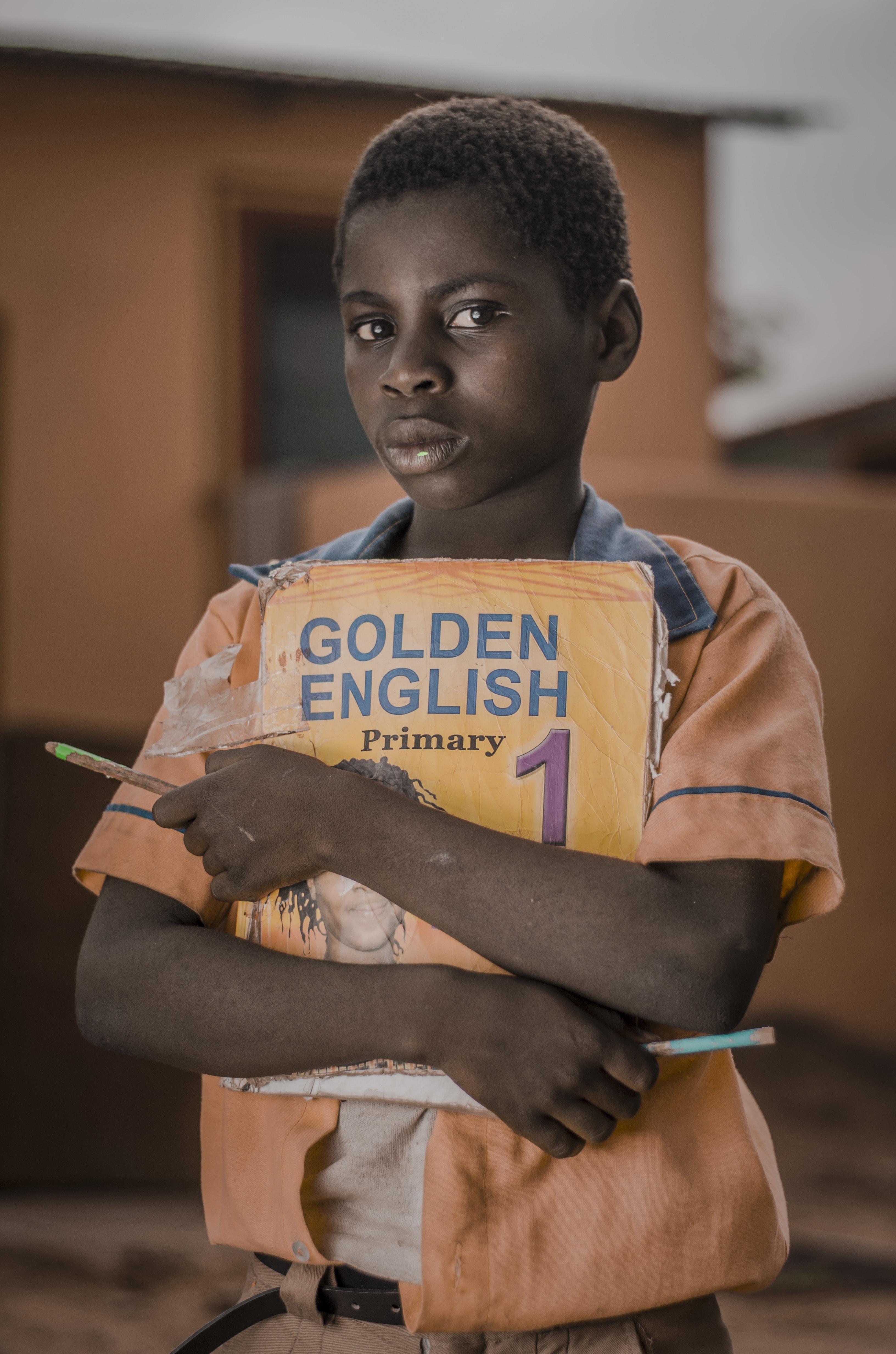 boy holding Golden English 1 book