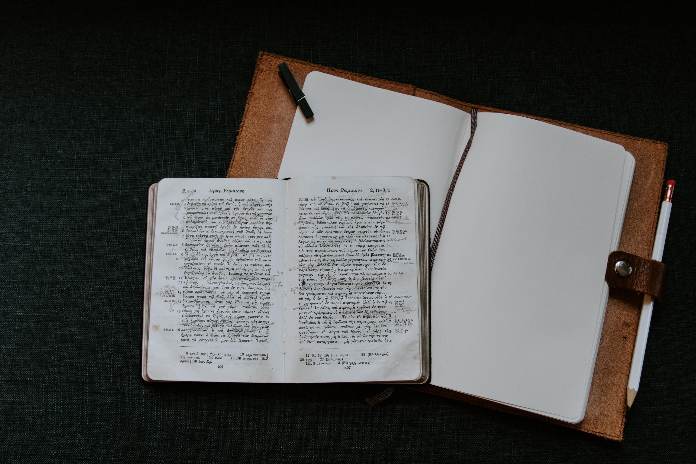 hardbound book on top of brown binder